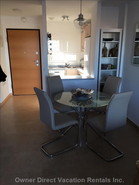 A View from the Lounge Area Showing the Entrance to the Apartment, the Dining Area and Kitchen.