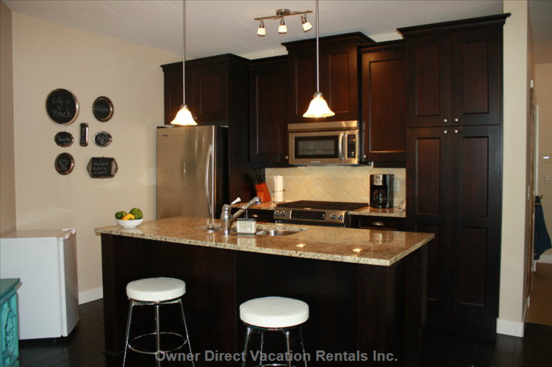 Executive Kitchen with Stainless Steel Appliances, Gas Stove and Eating Bar. Granite Counter Tops