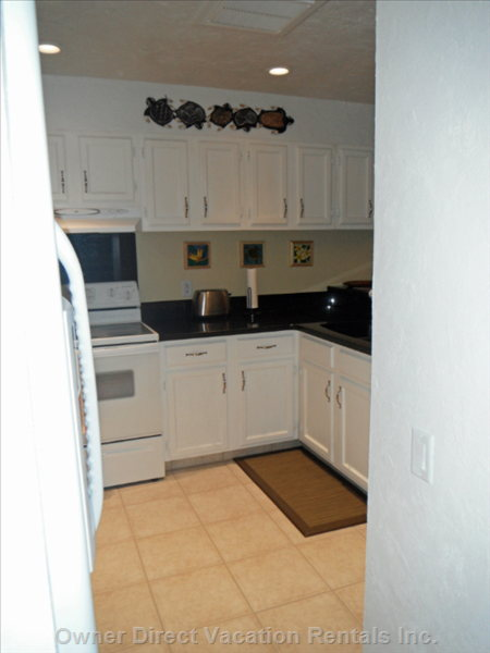 Remodeled Kitchen Organized with Full Size Refrigerator, Range, and Dishwasher, Microwave, Coffee Maker and Toaster.
