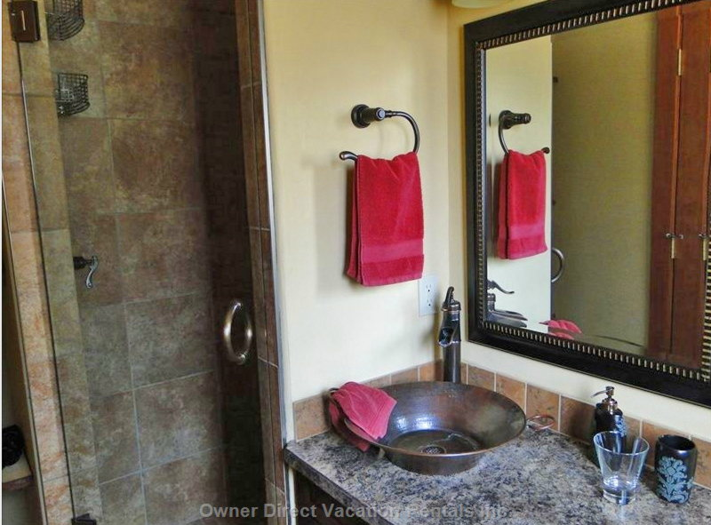 Hand Hammered Copper Vessel Sink in Bathroom with Tiled Custom Shower Stall.