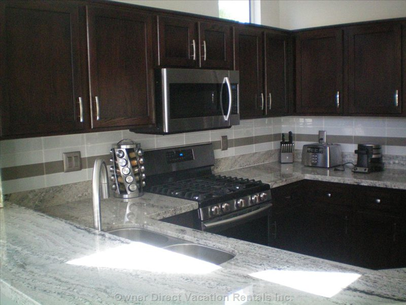 Kitchen with Slab Granite Counters and Eating Bar